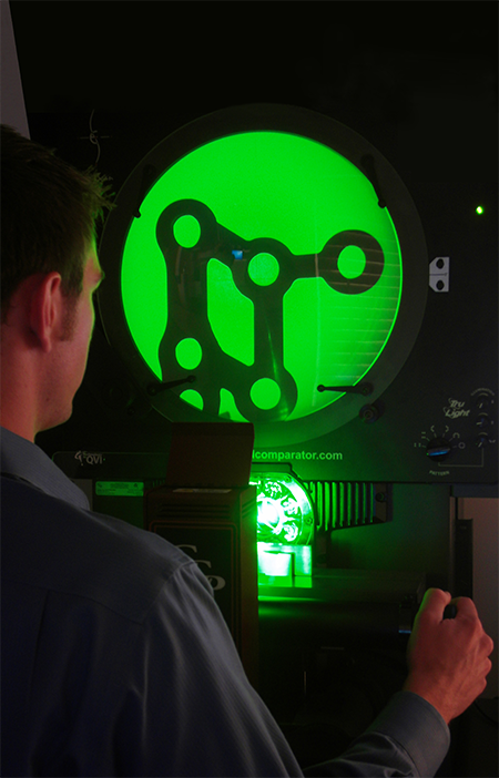 TraTek's Shaun Smyser inspects dimensional accuracy of a finished orthopedic plate on an optical comparator.